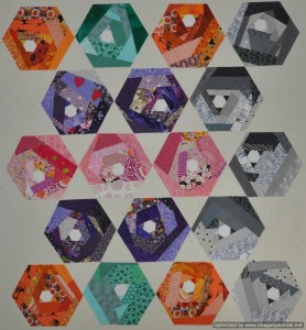 Scrappy Hexie blocks in orange, purple, grey, teal, and pink